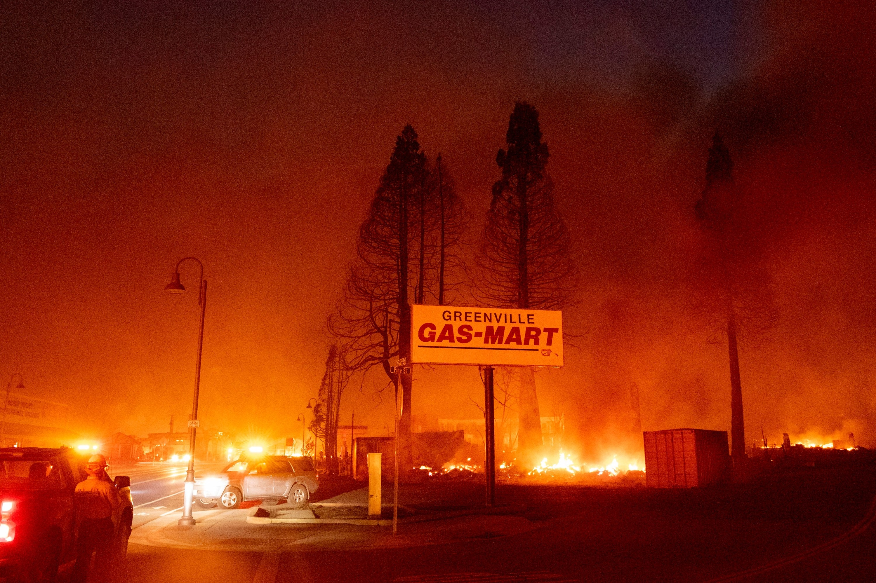 A sign for Greenville Gas Mart is surrounded by a fire under a smoky sky