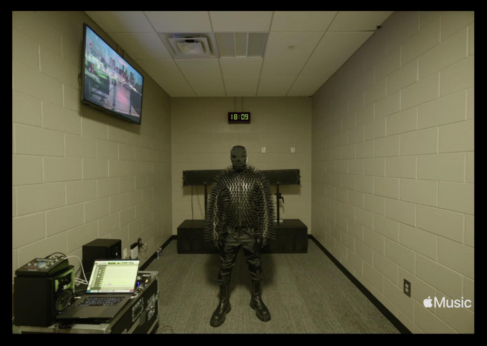 Kanye wears a spike-covered shirt, pants, boots, and a full face covering, standing in a concrete-lined room