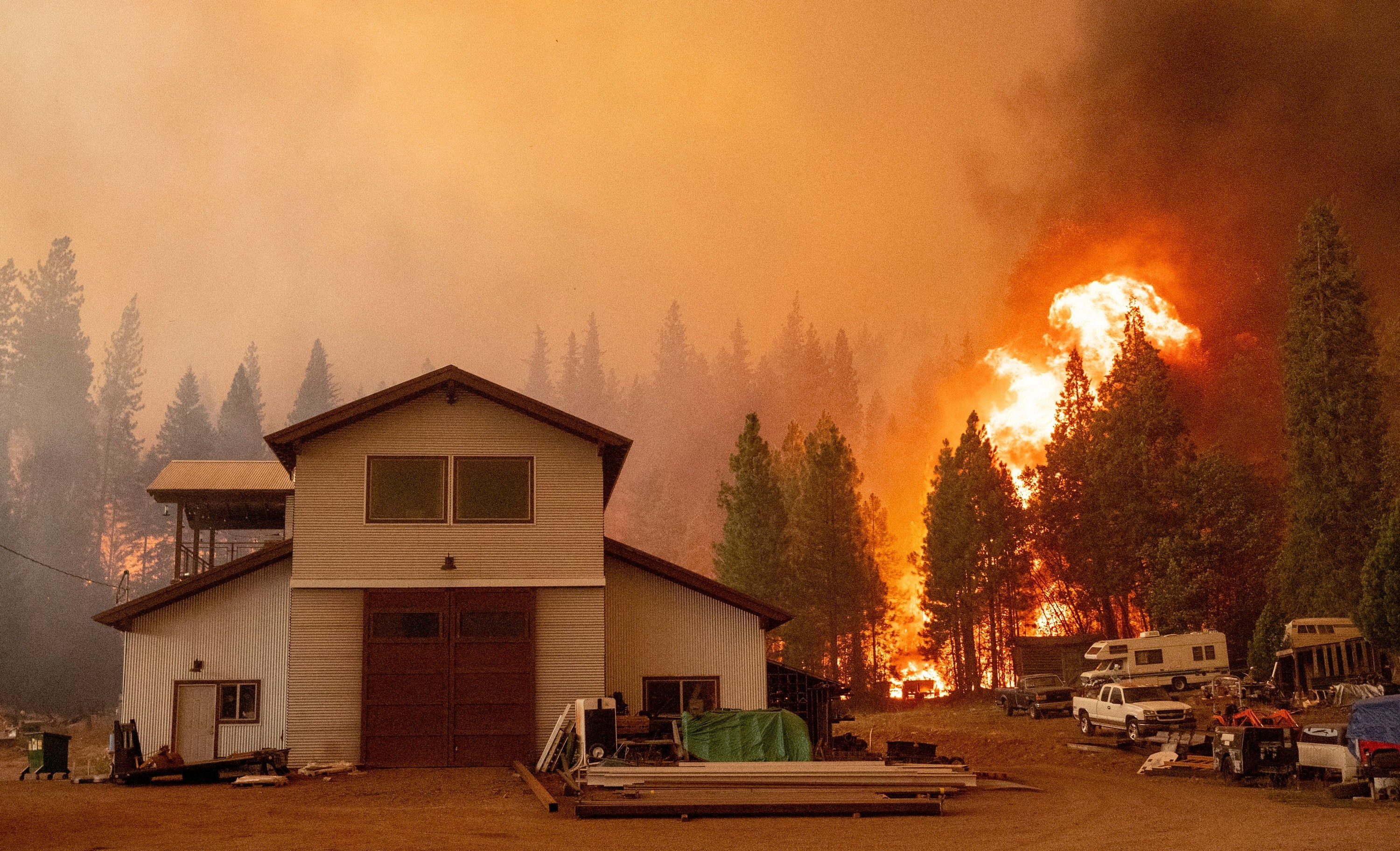 A two-story home with trucks and recreational vehicles parked outside is surrounded by a forest fire