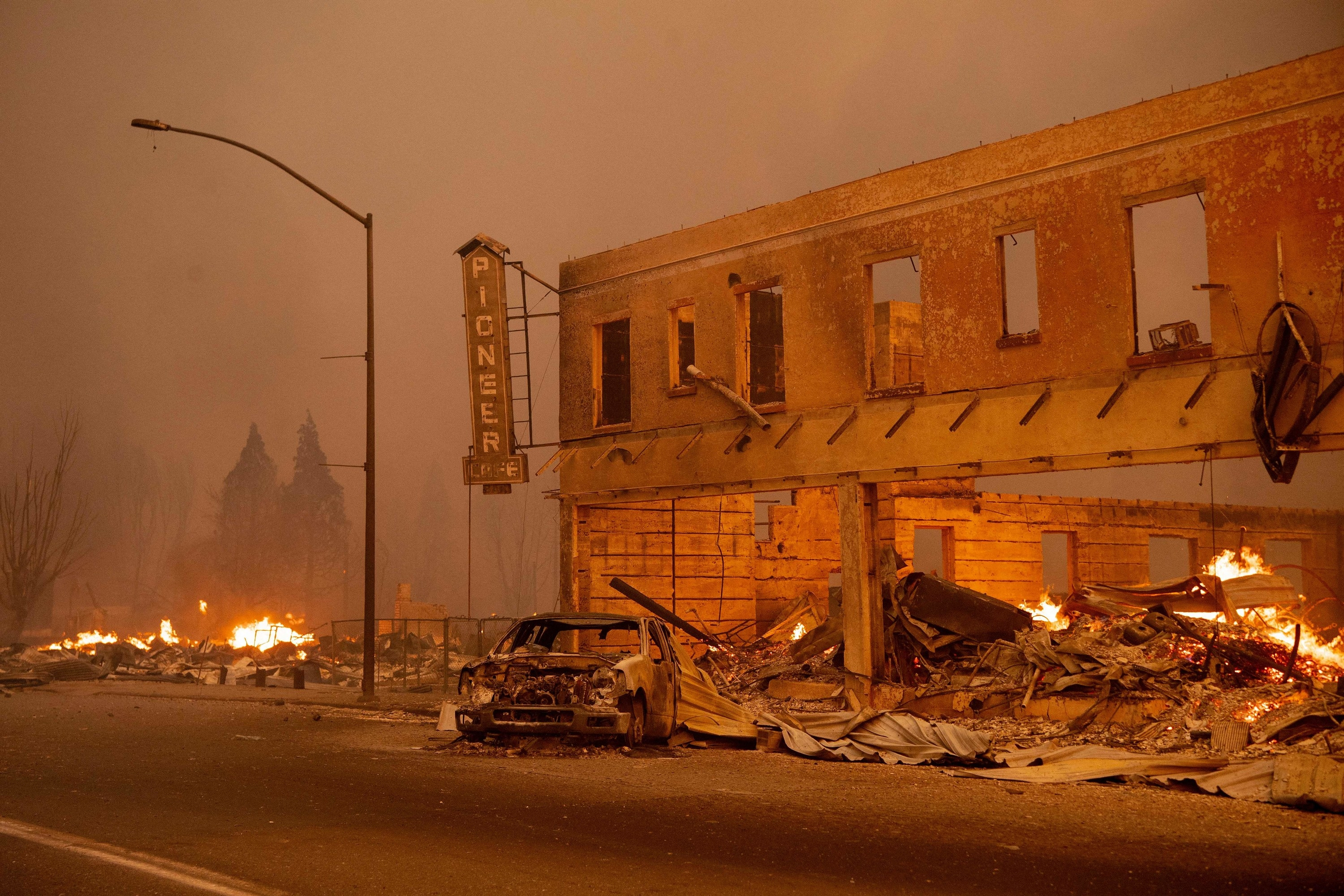 A hollowed-out two-story building is surrounded by flames, rubble, and a destroyed car