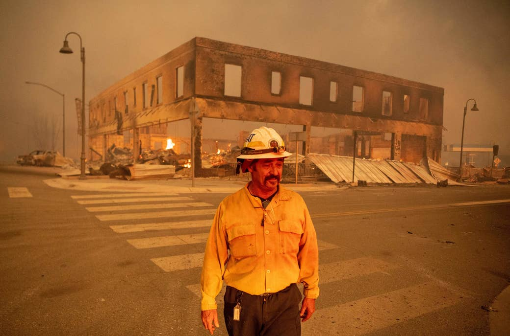 A firefighter stands in a smoky intersection in front of a destroyed two-story building