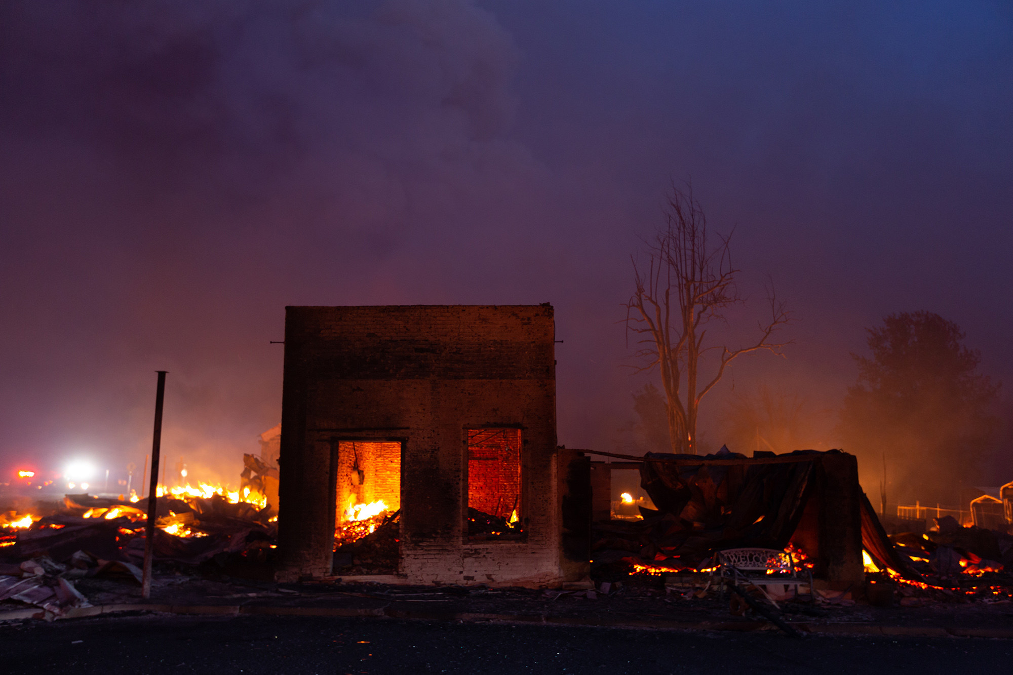 A destroyed brick building is surrounded by fire and debris