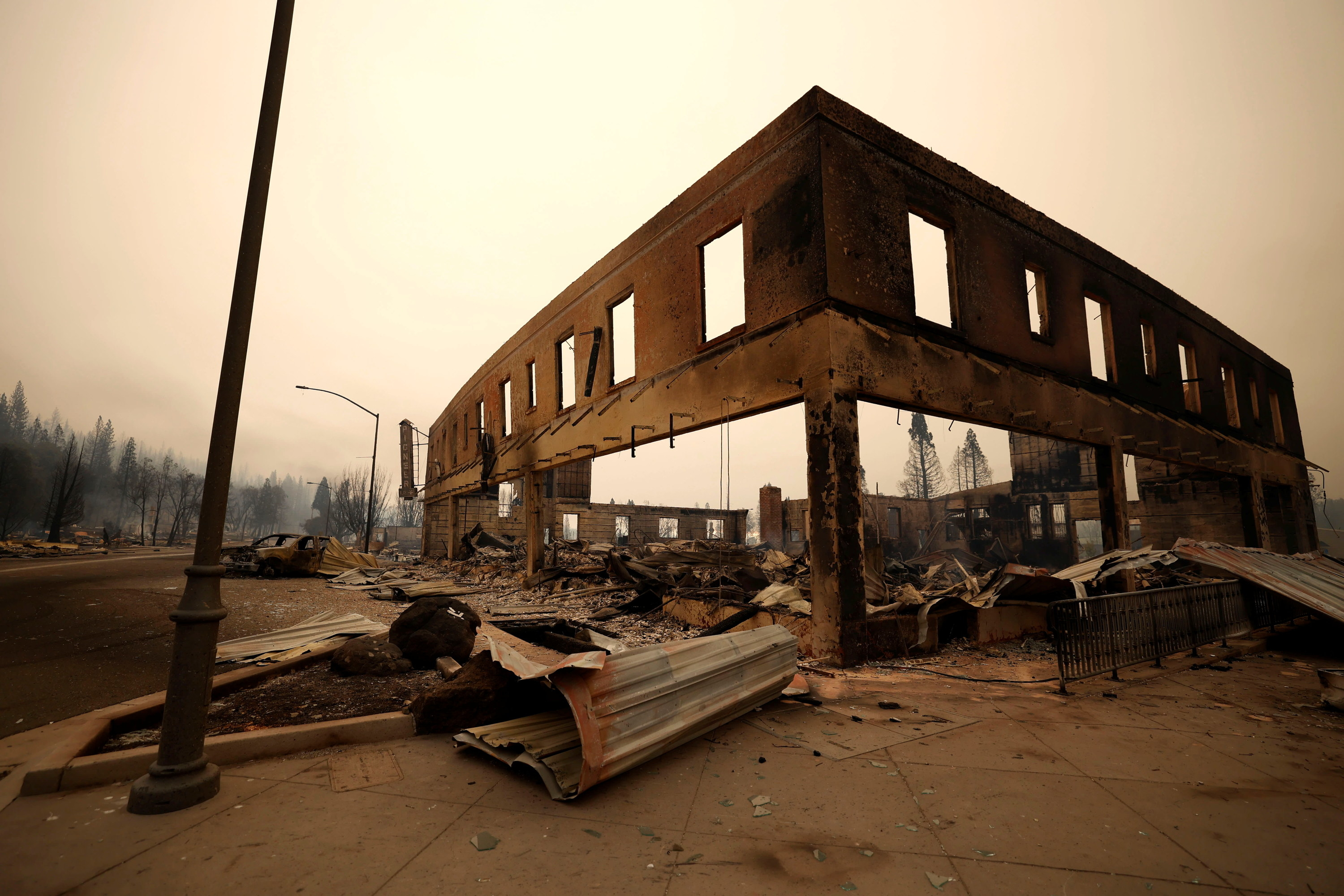 A building without windows or a roof is surrounded by debris under a smoky sky