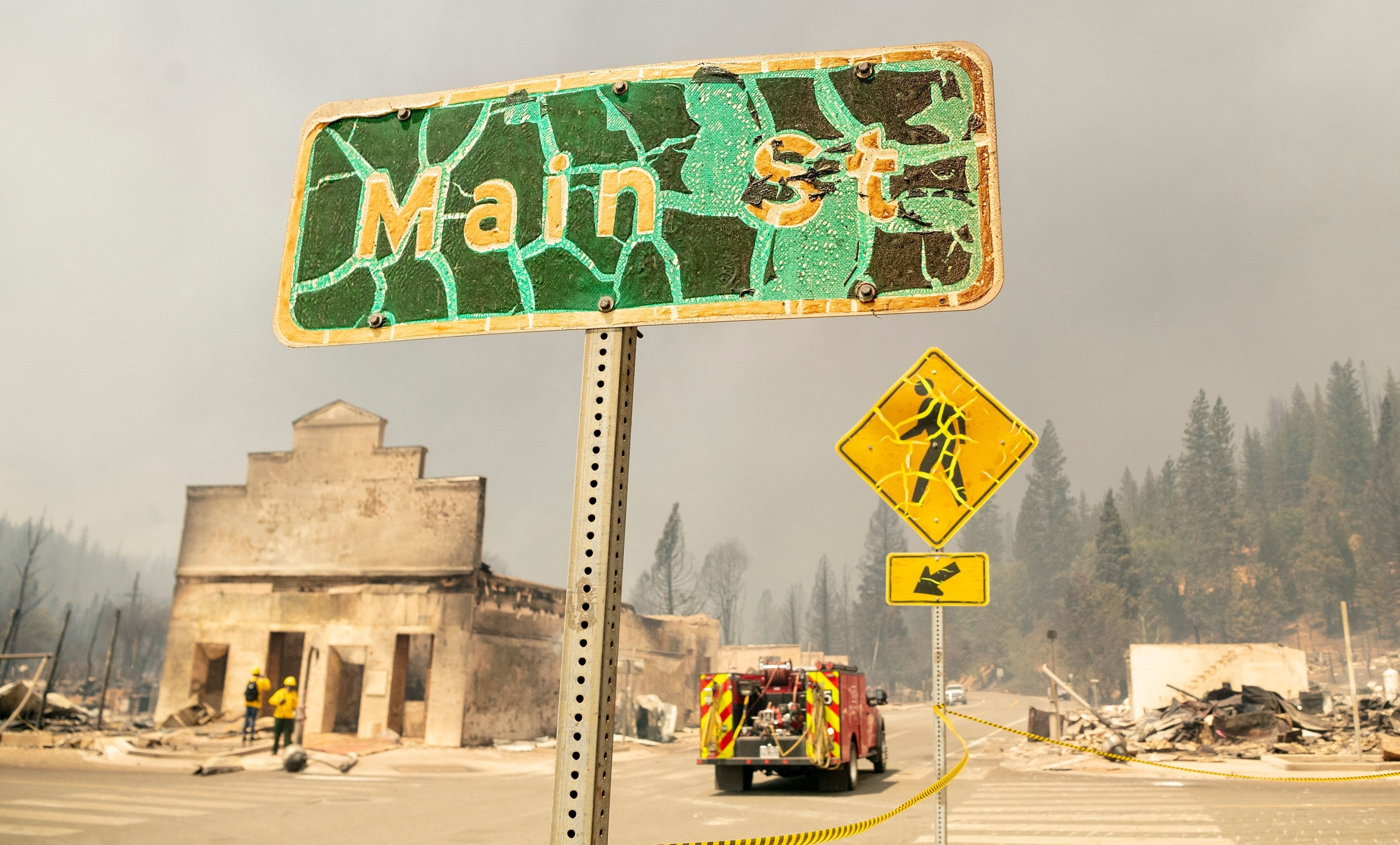 """The paint is cracked and warped on a crossing sign and a marker that reads """"Main Street,"""" surrounded by destroyed buildings and rubble"""