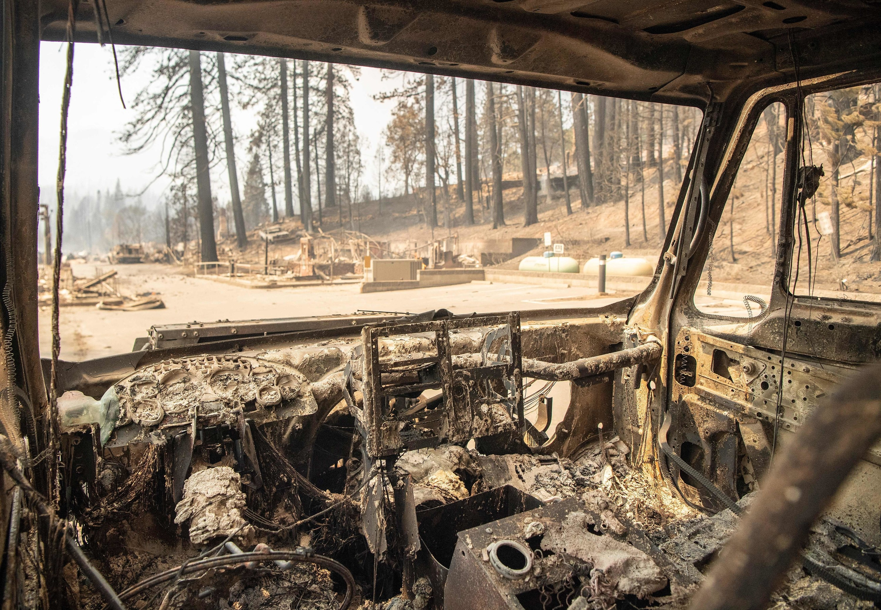 The inside of a car is destroyed, parked among desolation and burned-out debris