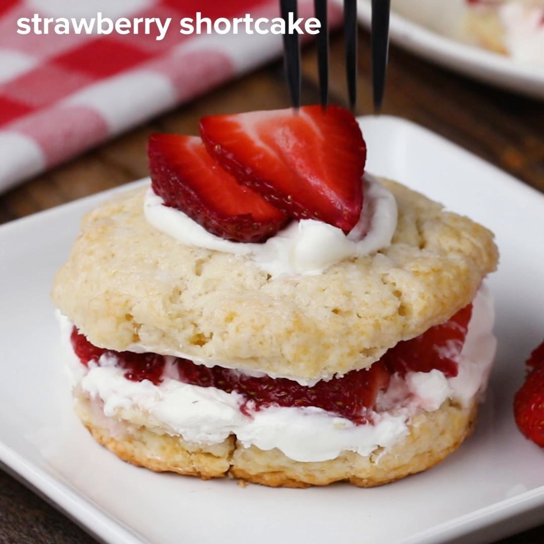 Frosting and strawberries sandwiched in-between shortbread biscuits and topped with cream and two sliced strawberries