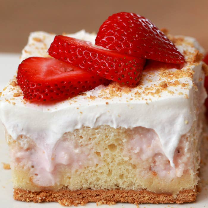A sponge cake with white frosting, sliced strawberries and a graham cracker sprinkled on top