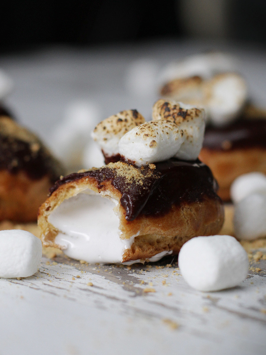 Mini éclairs filled with marshmallow fluff and topped with chocolate sauce, graham cracker sprinkled on top with toasted marshmallows