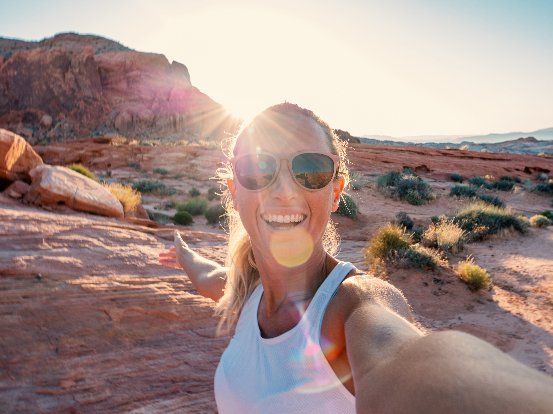 Woman takes photo in deserty surroundings