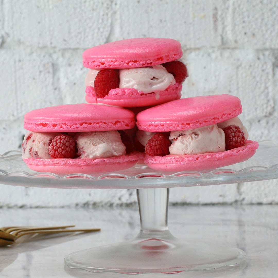 Three pink macarons filled with ice cream and berries