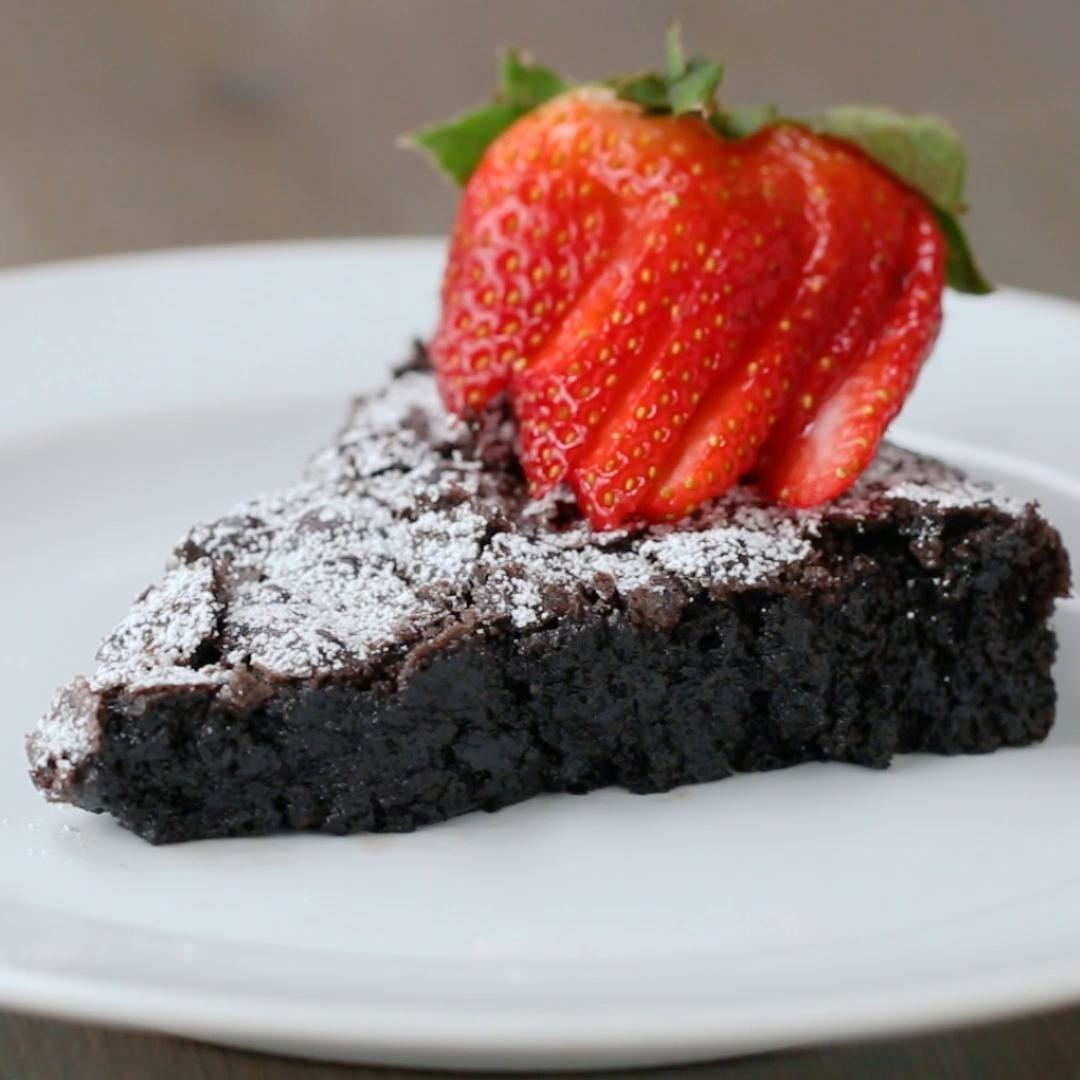 A dense slice of chocolate cake with icing sugar and sliced strawberries