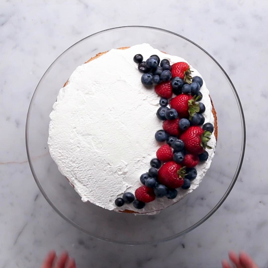 Mexican dessert with topped full of whipped cream and a variety of berries including blueberries, strawberries and raspberries
