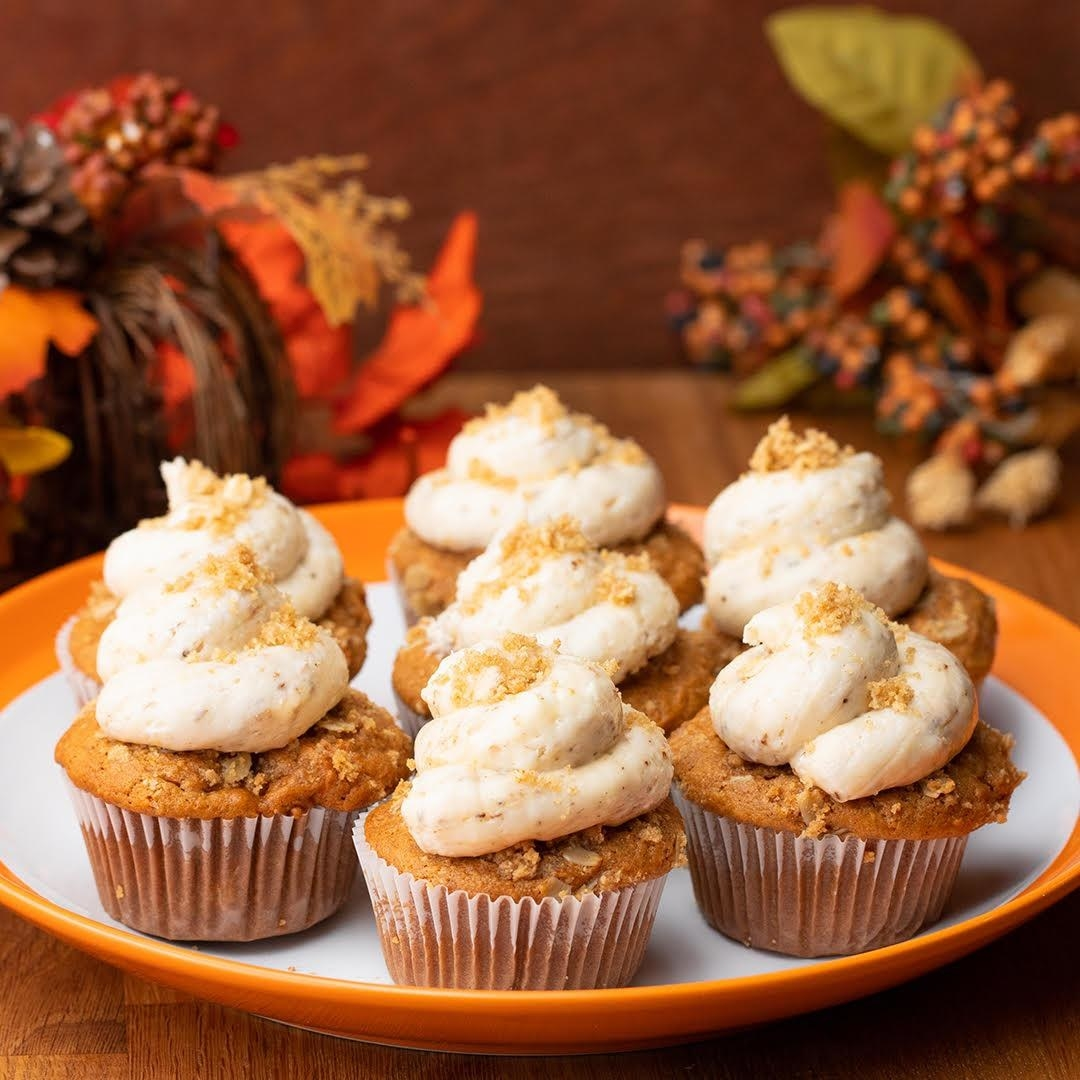Plate of seven pumpkin cupcakes topped with a dollop of marshmallow fluff sprinkled with crushed crackers