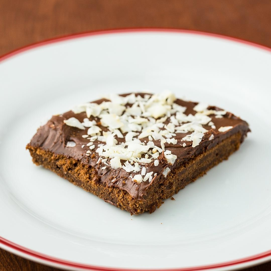 A square of sheet cake coated in thick chocolate sauce and topped with coconut