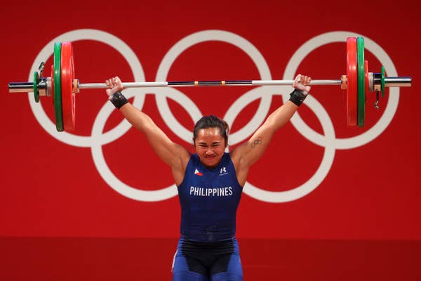 Hidilyn Diaz of Team Philippines lifts weights over her heard