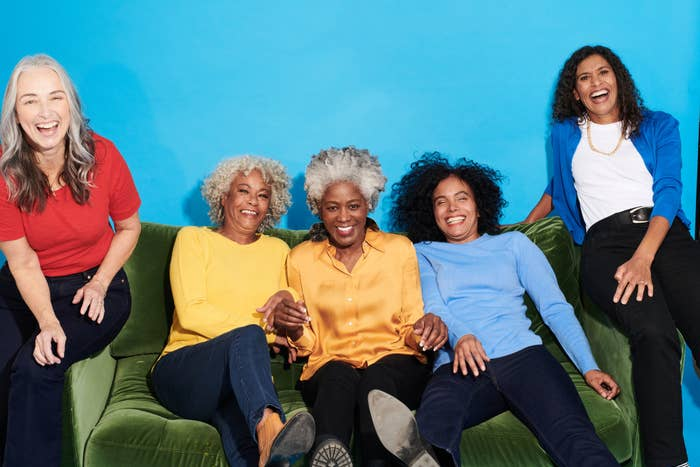 A group of women smiling as they sit on a couch