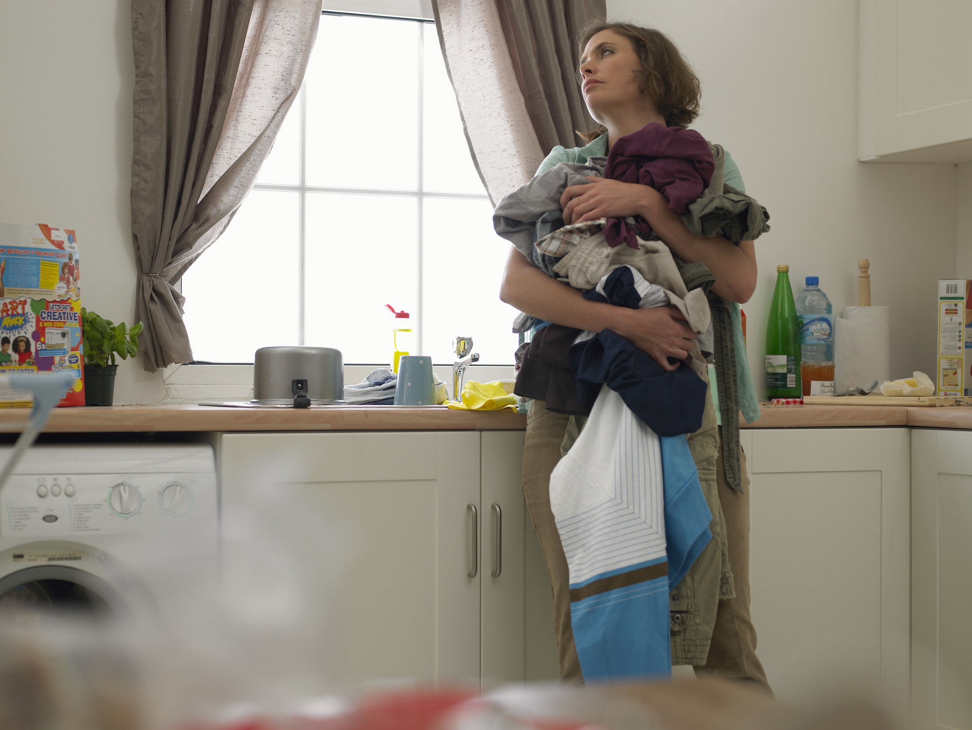 A woman holding a pile of laundry