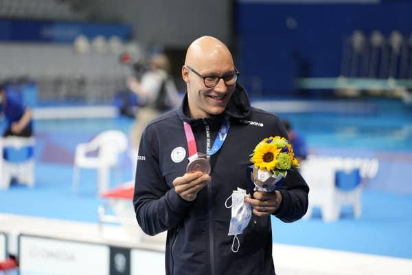 Matti Mattsson holds flowers and bronze medal