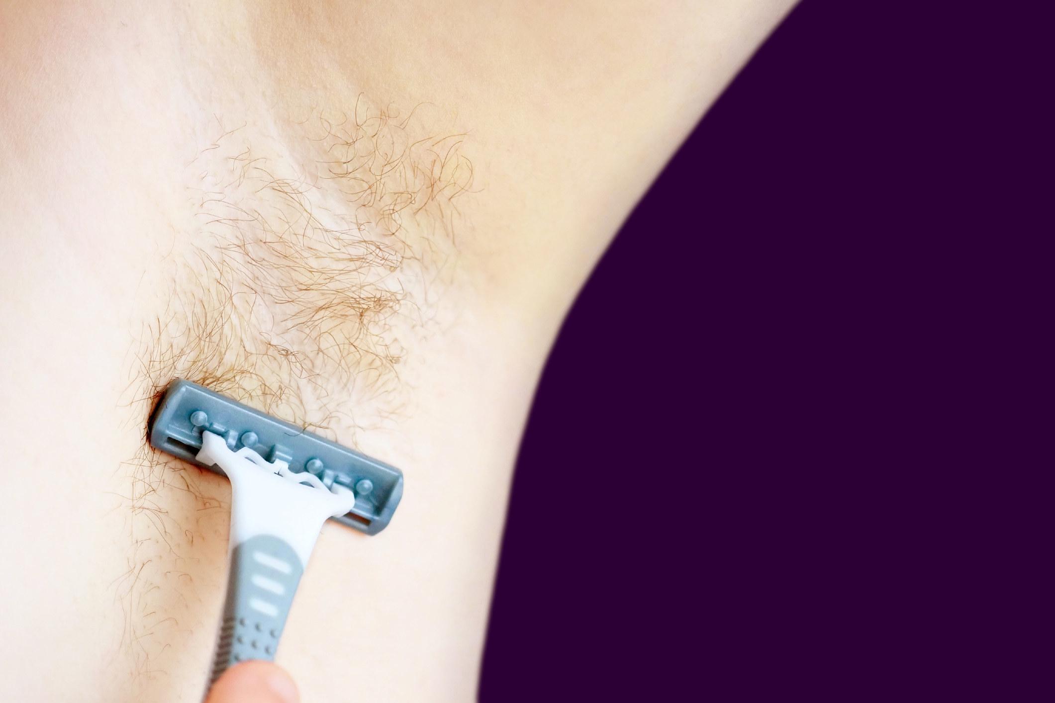 A person shaving their armpits