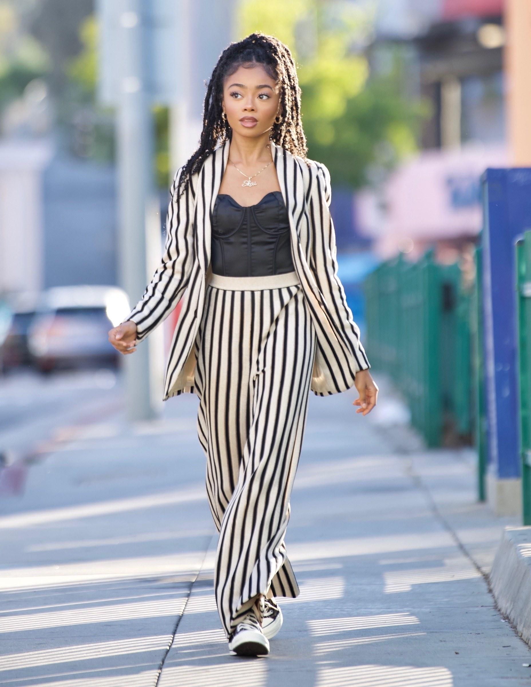 Skai Jackson wears a pinstripe pantsuit and black corset top while walking around in Los Angeles