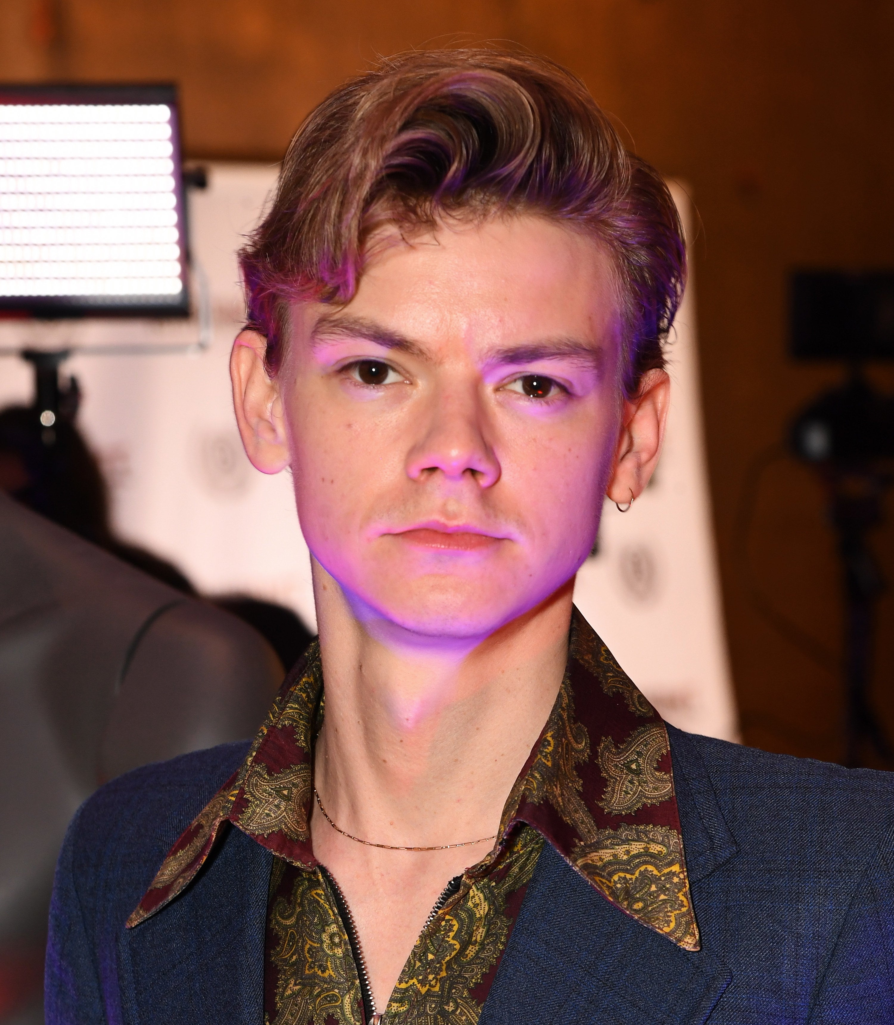 Thomas Brodie-Sangster wears a navy suit and minimalist jewelry at the 28th Raindance Film Festival