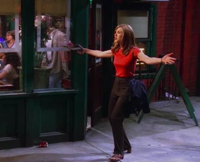 Rachel wearing slim pants, a red shirt, and a cute off-the-shoulder bag, but also weird sandal heels
