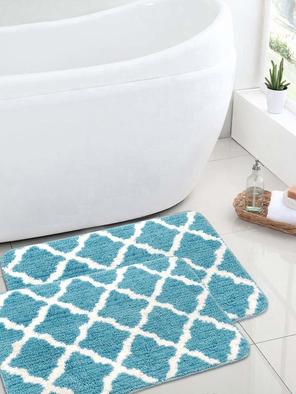 Two turquoise bath mats next to a bath tub