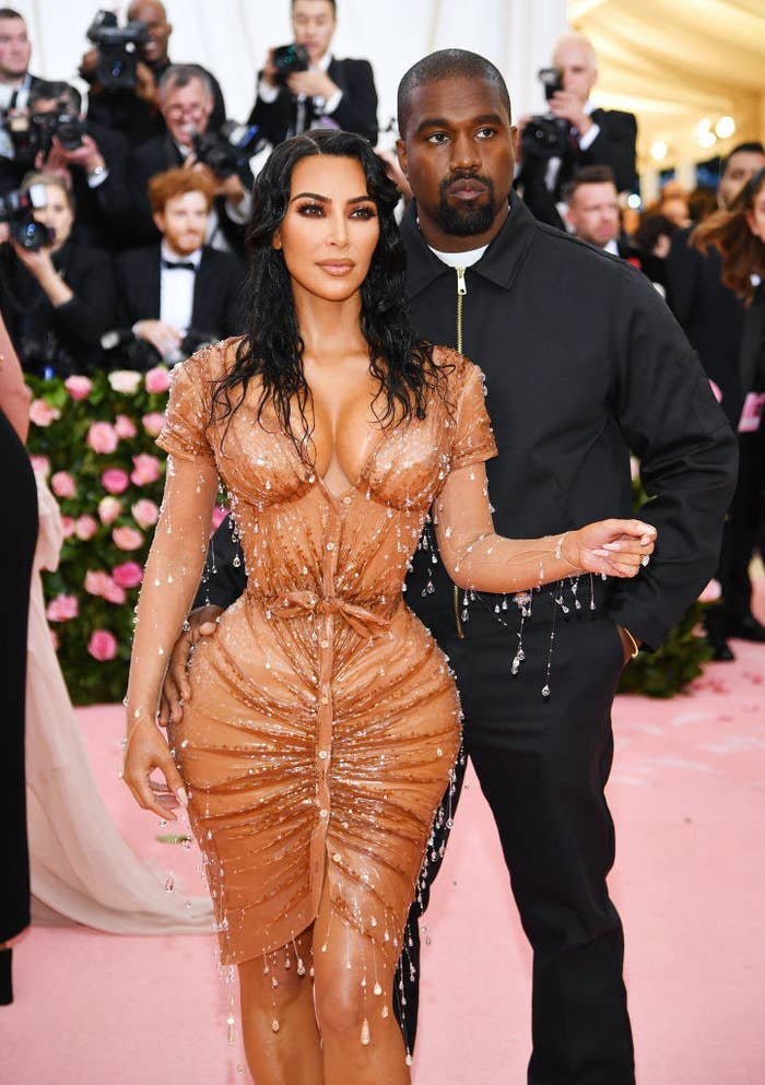 Kim wearing a tight latex-like dress while at the Met Gala with Kanye, who wore a casual jacket and matching pants