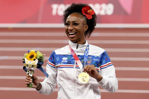 Jasmine Camacho-Quinn poses with flowers and Women's 100m Hurdles gold medal