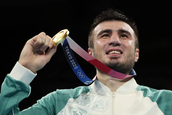 Bakhodir Jalolov of Uzbekistan holds gold medal up