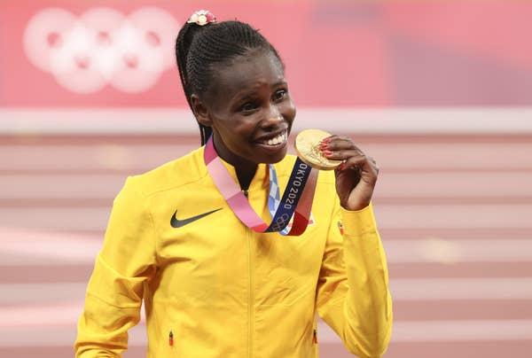 Peruth Chemutai of Uganda smiles with gold medal