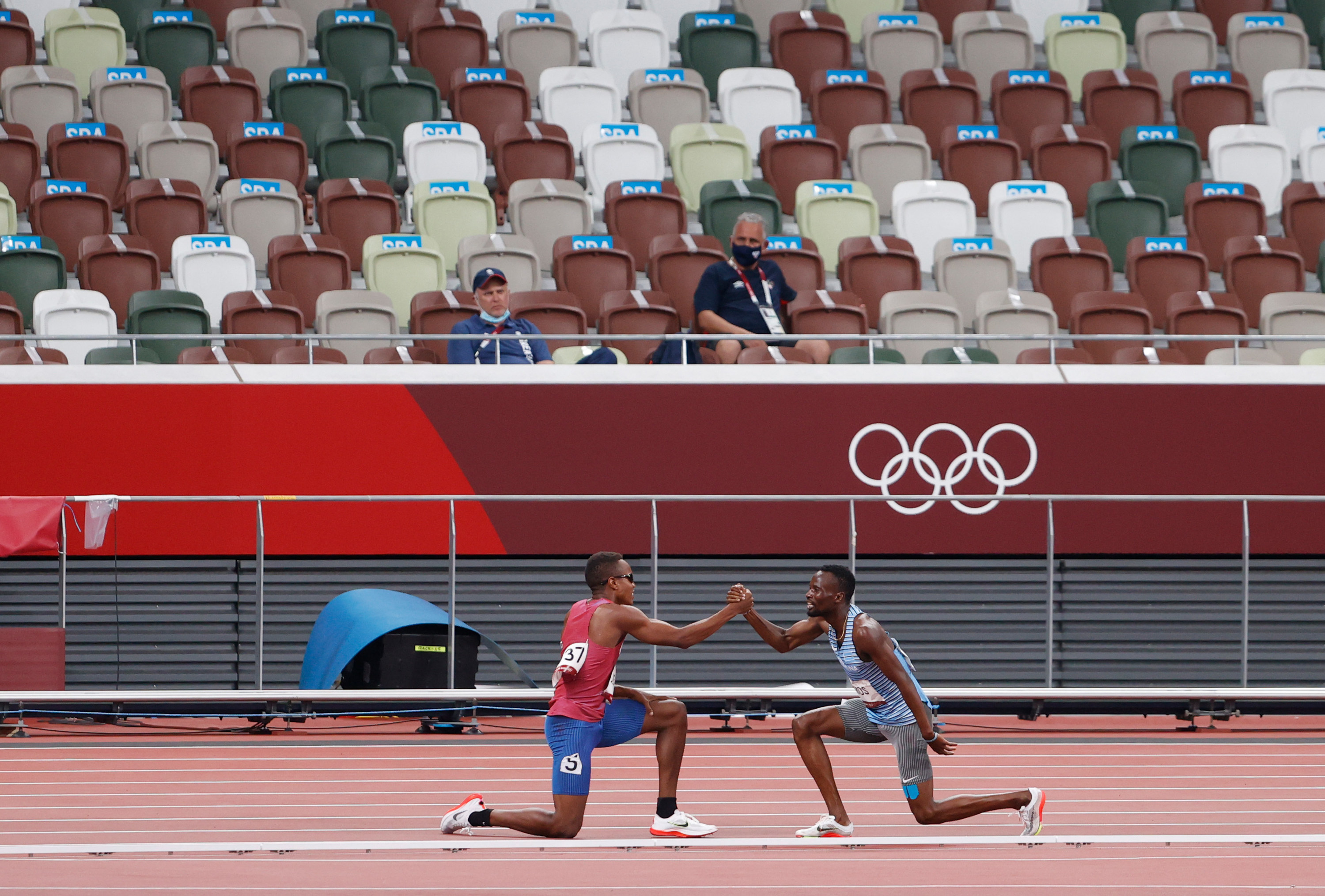 Isaiah and Nijel kneel on one knee and clasp hands on the track