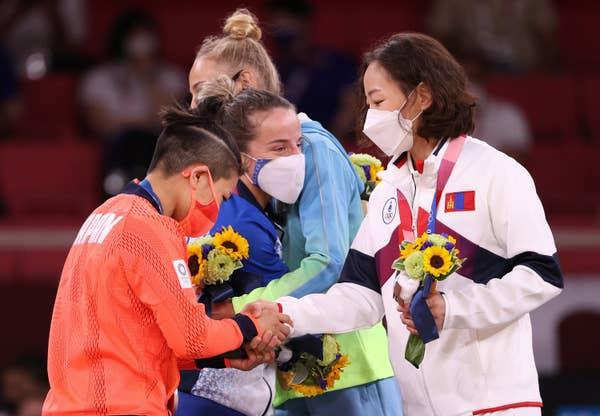 Urantsetseg Munkhbat of Team Mongolia shakes hands at award ceremony
