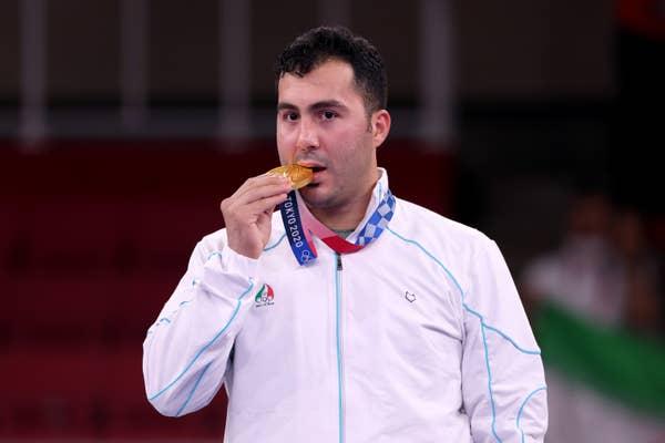 Sajad Ganjzadeh of Team Iran bites his gold medal in celebration