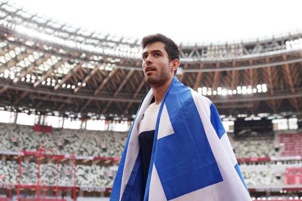 Miltiadis Tentoglou of Team Greece draped in Greek flag