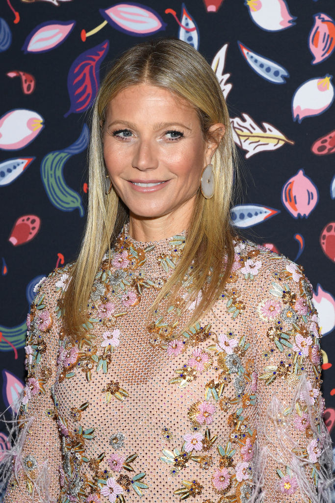 Gwyneth Paltrow poses in an intricate sheer flower-adorned beige-colored dress at Harper's Bazaar Exhibition At Musee Des Arts Decoratifs In Paris