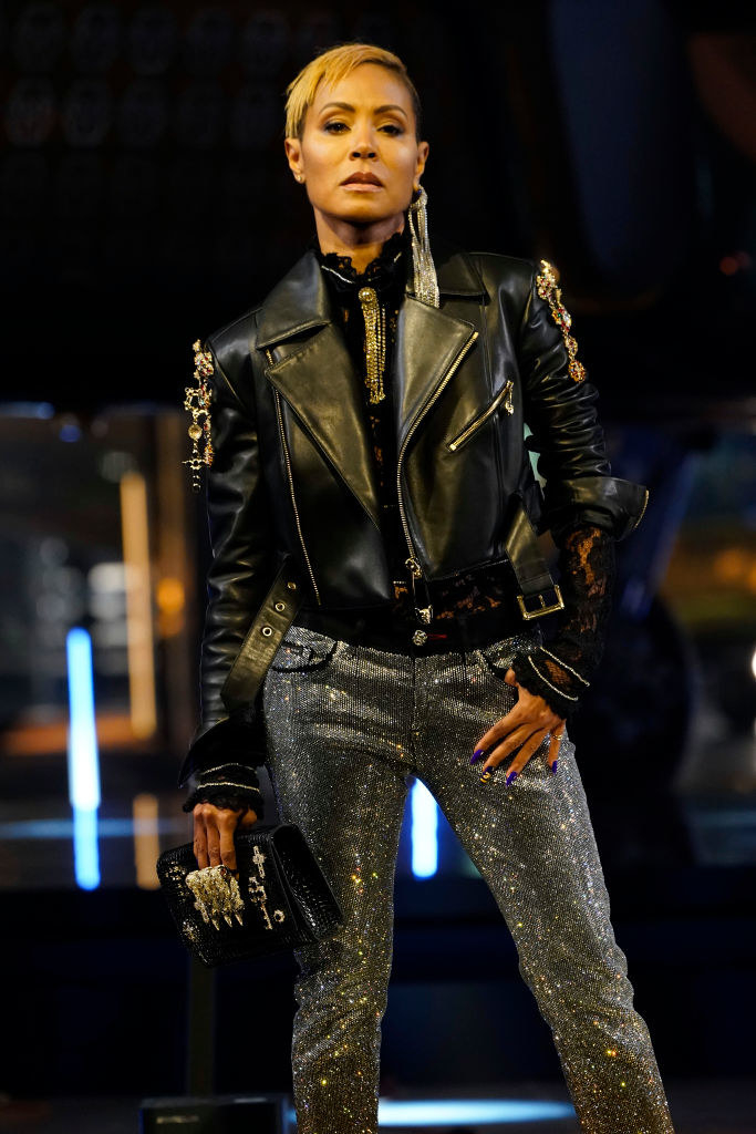 Jada Pinkett Smith poses at Milan Fashion Week, wearing a black leather jacket with chunky decorations that matches her clutch and sequined pants