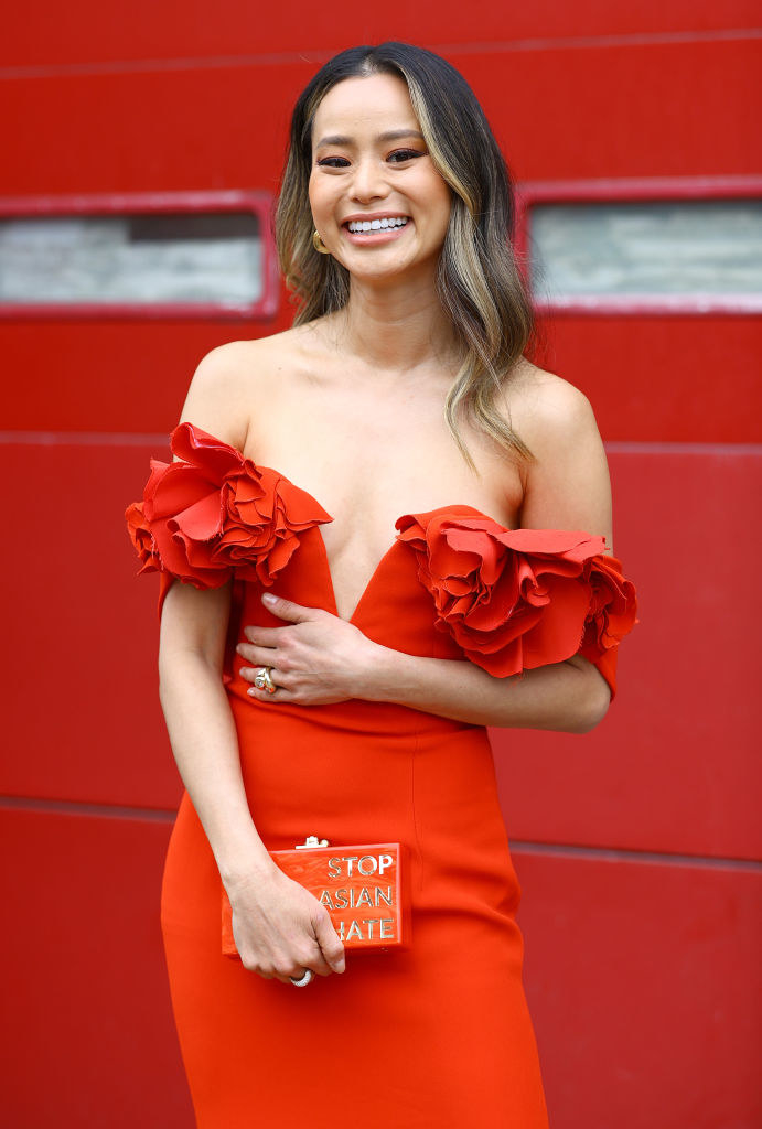 """Jamie Chung wears a red strapless dress to the 27th Annual SAG Awards and carries a matching clutch that reads """"STOP ASIAN HATE"""""""