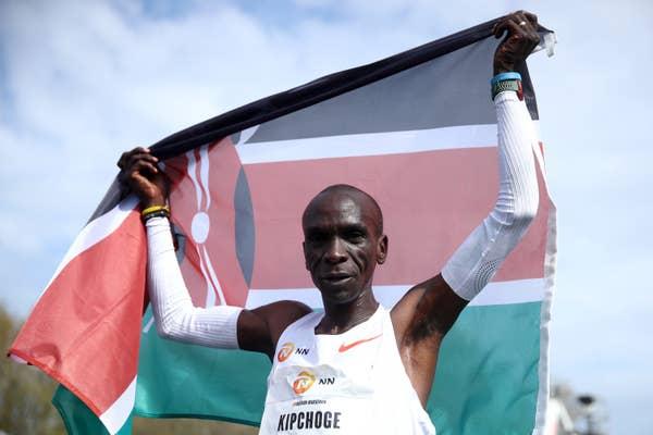 Eliud Kipchoge of Kenya raises his flag