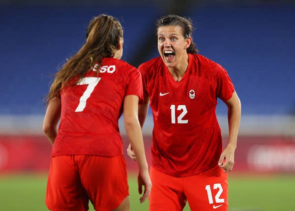 Canadian soccer player Christine Sinclair celebrates with teammate Julia Grosso