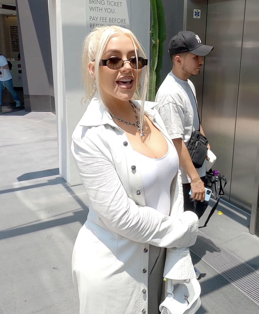 Christina Aguilera wears an all white outfit with silver jewelry and black shades while sighted in Los Angeles