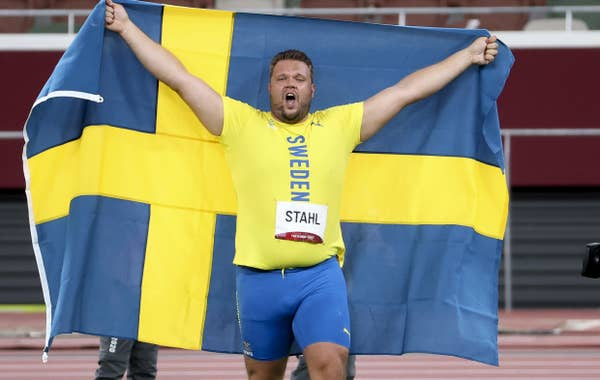Daniel Stahl of Sweden celebrates with country's flag draped over him