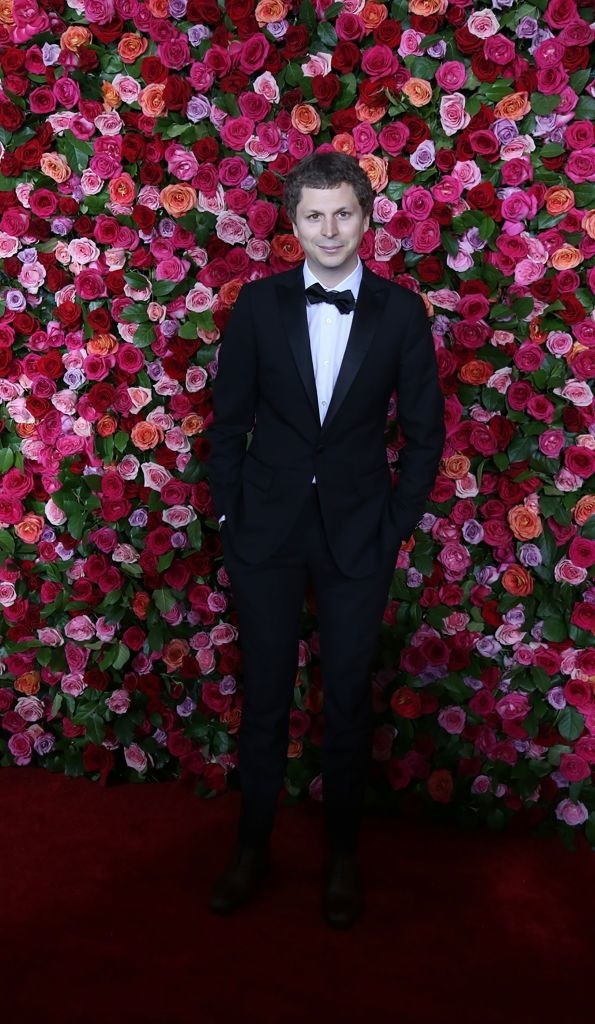 Michael Cera in a black tux stands in front a wall of roses at the 72nd Annual Tony Awards