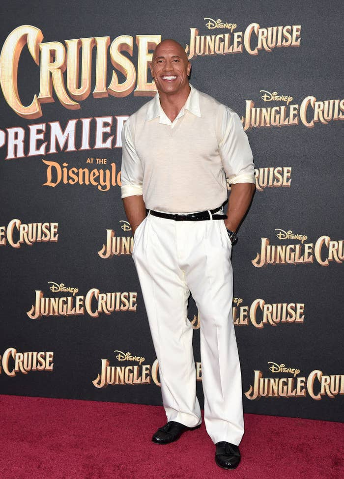 """Dwayne Johnson attends the World Premiere of Disney's """"Jungle Cruise"""" in a light-colored shirt and vest with matching pants"""