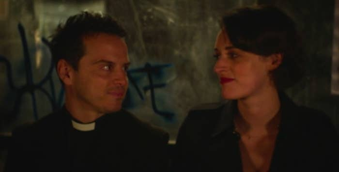 Hot Priest and Fleabag look at each other with soft smiles while sitting at a bus stop covered in graffiti