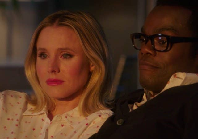 Eleanor and Chidi sit side by side looking emotional