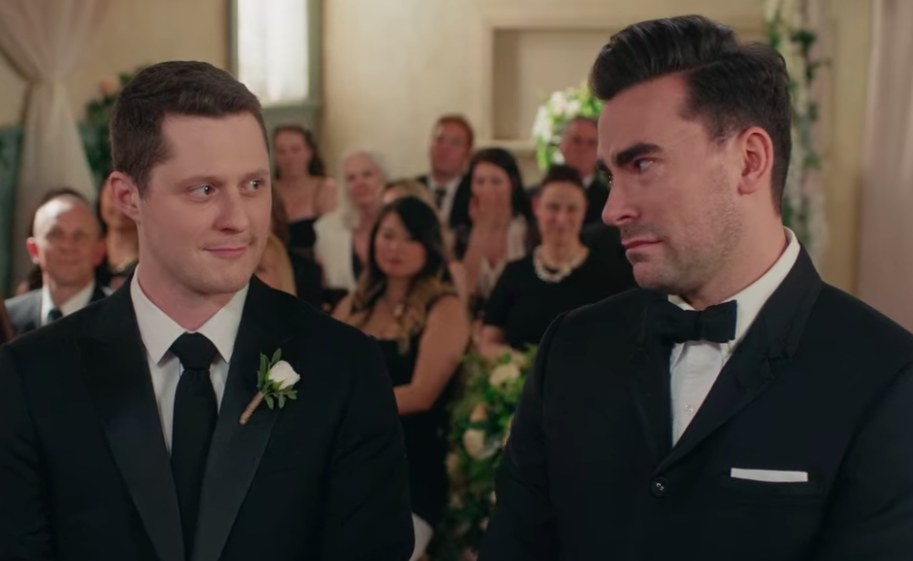 Patrick and David look at each other with emotion wearing suits and standing in front of their wedding guests