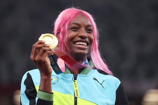 Shaunae Miller-Uibo of Team Bahamas holds up her gold medal