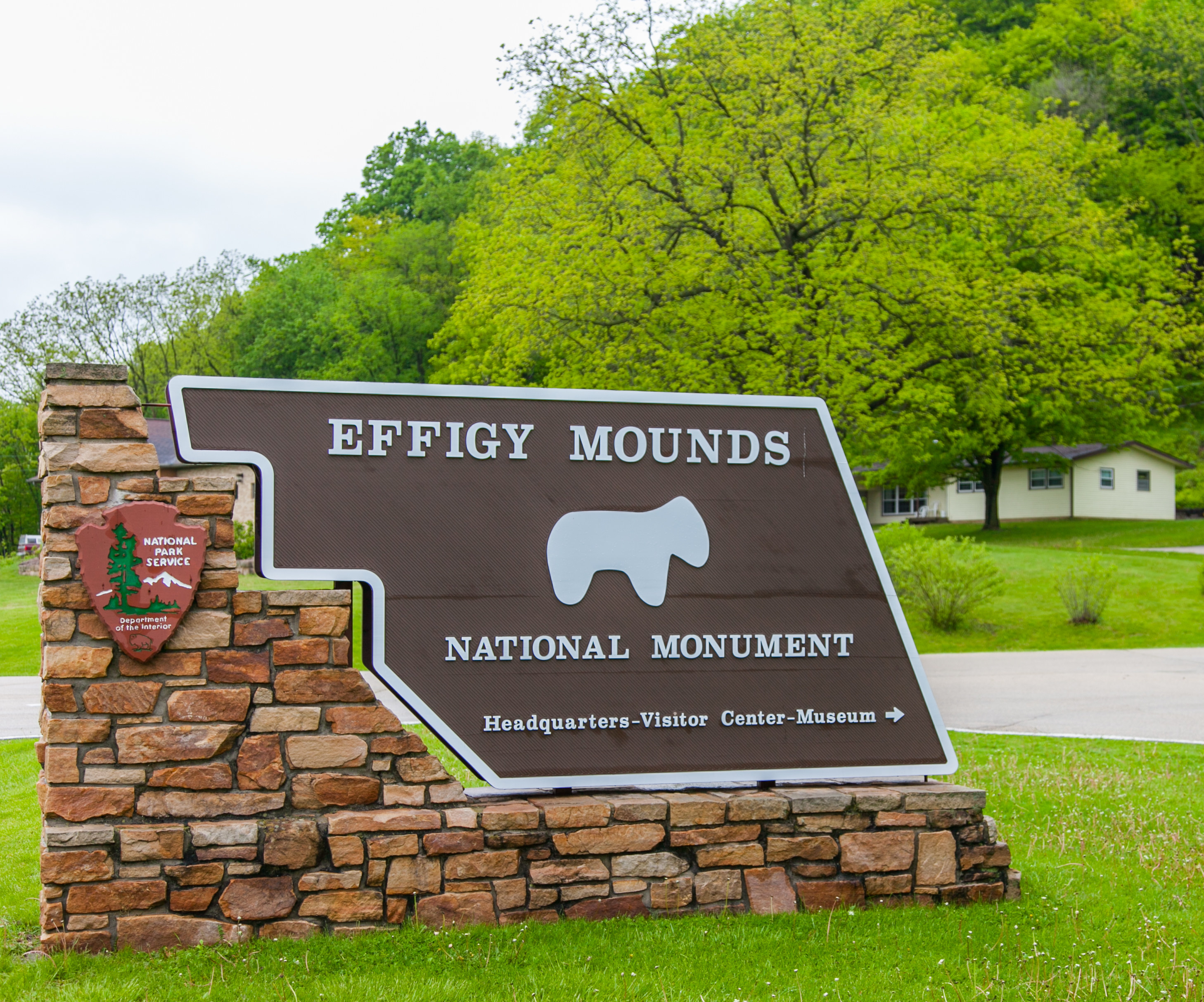 """A sgn reads, """"Effigy Mounds National Monument"""" and points in the direction of the """" headquarters, visitor center, museum"""""""