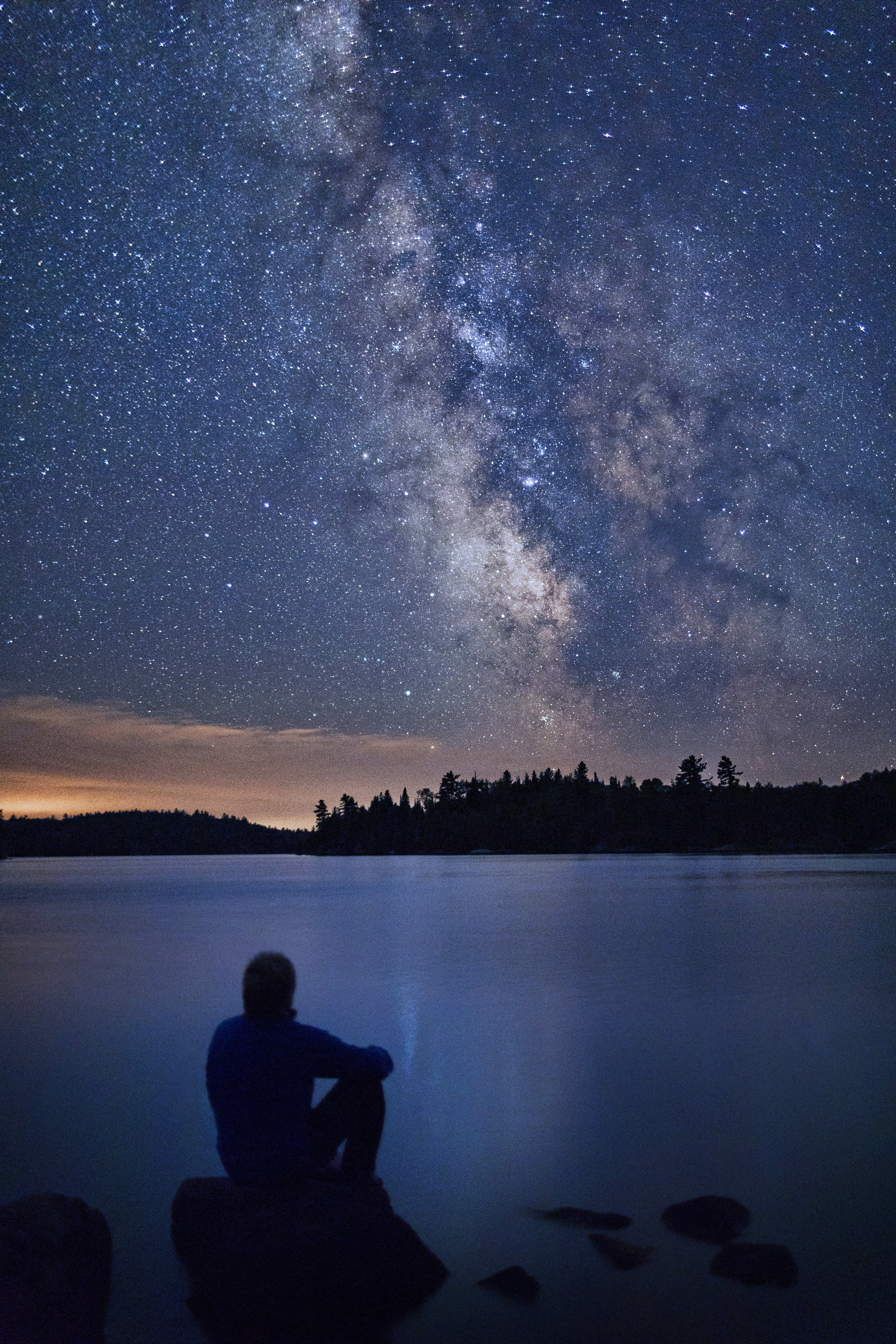 A man sits on a large boulder while looking out onto the dark and starry skies of Voyageurs national park.